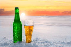Napadać na kogoś przy zmierzchem i butelka zimny piwo w śniegu piękna tła nosicieli ilustracyjna zimy plenerowy lunchu odtwarzani zdjęcie stock