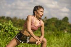 Napadu i sporty w średnim wieku biegacza kobiety rozciągania Azjatycka noga i ciało po działającego treningu na zieleni pola pięk zdjęcia royalty free
