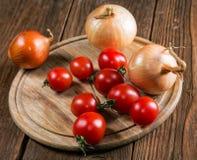 Napiform tomater för lökar på en gammal tabell Royaltyfri Foto