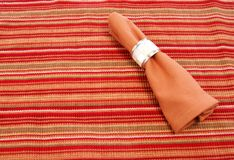 Napkin. Cloth napkin with decorative napkin ring on striped placemat Royalty Free Stock Images
