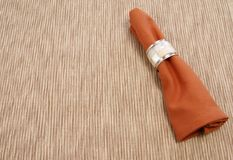 Napkin. Cloth napkin with decorative napkin ring on neutral placemat Royalty Free Stock Image