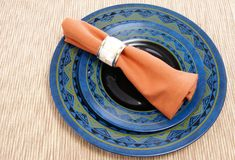 Napkin. Cloth napkin with decorative napkin ring on western style black and blue plates Royalty Free Stock Images
