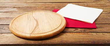 Napkin and board for pizza on wooden desk closeup, tablecloth. Canvas, dish towels on white wooden table background top view mock. Up. Selective focus stock image