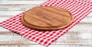 Napkin and board for pizza on wooden desk closeup, tablecloth. Canvas, dish towels on white wooden table background top view mock. Up. Selective focus royalty free stock photography