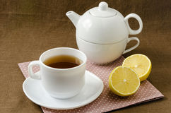 On napkin cup of tea with lemon in saucer and teapot. On a napkin cup of tea with lemon in a saucer and teapot, breakfast concept Royalty Free Stock Photography