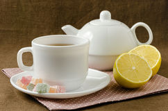 On napkin cup of tea with lemon in saucer and teapot. On a napkin cup of tea with lemon in a saucer and teapot, breakfast concept Royalty Free Stock Image