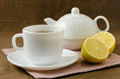 On napkin cup of tea with lemon in saucer and teapot Stock Photos