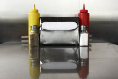 Napkin dispenser and condiments Royalty Free Stock Photos