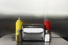 Napkin dispenser and condiments stock photography