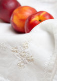 Napkin Embroidery and Nectarines Royalty Free Stock Images