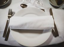 Napkin on an empty round white plate with cutlery on the sides stock image