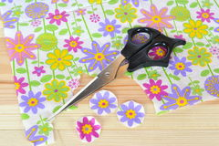 Napkin with flower pattern, scissors, cut paper pieces to decoupage on a wooden table. Home made paper craft Stock Photography