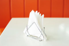 Napkin holder with white napkins on red background Royalty Free Stock Images