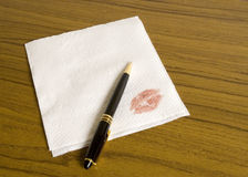 Napkin and a kiss 2. Blank cocktail napkin for your message, pen and a lipstick imprint Royalty Free Stock Images