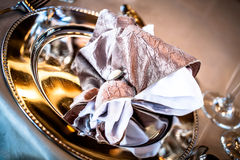 Napkin on silverware. A cropped image of a champagne and white napkin in a napkin ring placed on a silver plate Royalty Free Stock Photos