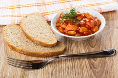 Napkin, slices of bread, beans with vegetables and tomato sauce, dill in bowl, fork on table. Checkered napkin, slices of bread, beans with vegetables and tomato royalty free stock images