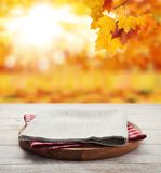 Napkin. Stack of colorful dish towels on wooden table and autumn background. Top view mock up royalty free stock photography