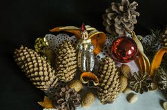 Napkin with with various pine cones, fir branch, old worn Christmas toys, almonds and orange peel on a black background. Paper napkin with with various pine royalty free stock photography