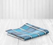 napking在与空的空间的白色木背景的蓝色布料 免版税库存图片