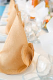 Napkins on plates in perspective. Golden napkins folded as cones on plates, in perspective, on laid banquet table, shallow DOF Stock Photo