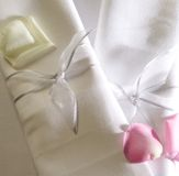 Napkins and rose petals. A set of napkins tied with a ribbon and pink and ivory rose petals Royalty Free Stock Photo