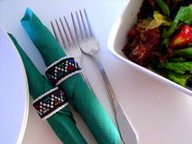 Napkins & Salad 2. Photo of a dinner setting featuring a salad, napkins and African beaded napkin rings stock photo