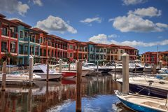 Long exposure of boats in a marina. Naples, Florida, USA – October 20, 2017: Long exposure of boats in a marina with colorful buildings in Naples, Florida, USA Royalty Free Stock Image