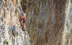 NAPLES ITALIEN -04 September 2017: en oidentifierad och idrotts- kvinna klättrar ett berg nära havet på en varm sommar Royaltyfri Foto