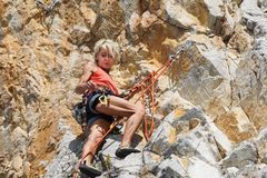 NAPLES ITALIEN -04 September 2017: en oidentifierad och idrotts- kvinna klättrar ett berg nära havet på en varm sommar Arkivfoton