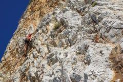 NAPLES ITALIEN -04 September 2017: en oidentifierad och idrotts- kvinna klättrar ett berg nära havet på en varm sommar Arkivfoto