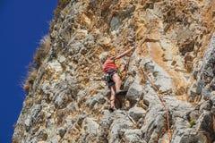 NAPLES ITALIEN -04 September 2017: en oidentifierad och idrotts- kvinna klättrar ett berg nära havet på en varm sommar Royaltyfri Bild