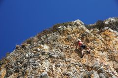NAPLES ITALIEN -04 September 2017: en oidentifierad och idrotts- kvinna klättrar ett berg nära havet på en varm sommar Royaltyfri Fotografi
