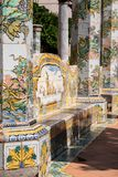 Colourful tiled pillars and bench in the cloister garden at the Santa Chiara Monastery in Via Santa Chiara, Naples Italy. Naples Italy. Colourful tiled pillars royalty free stock photography