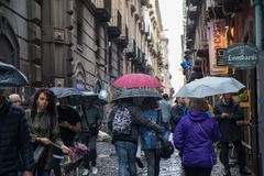 NAPLES, ITALY - 04 November, 2018. People walking in the rain under an umbrella. stock images