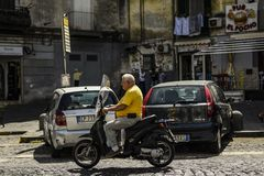 Old man riding a scooter in Naples. stock photography