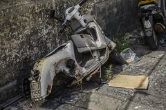 Wreck of white scooter, rusted, damaged, abandoned. stock image