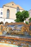 Naples - Santa Chiara Cloister. A bench decorated with maiolica from Santa Chiara Cloister in Naples, Italy. Santa Chiara Church in the background Royalty Free Stock Photo