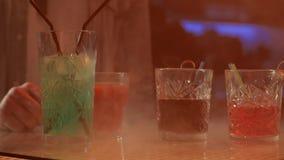 Napoje w szkłach z słoma na barze odpierającym w dymu na tle barwione lampy zdjęcie wideo