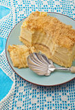 Napoleon cake on a plate on blue tablecloth Stock Images