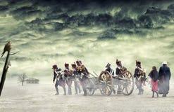 Napoleonic soldater och kvinnor som marscherar och drar en kanon i vanligt land, bygd med stormiga moln Gå för soldater Fotografering för Bildbyråer