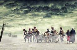 Napoleonic soldater och kvinnor som marscherar och drar en kanon i vanligt land, bygd med stormiga moln Soldater som går in mot Royaltyfri Bild