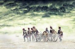 Napoleonic soldater som marscherar och drar en kanon i vanligt land Bygd med stormiga moln Soldater som går in mot Arkivbild