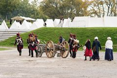 Napoleonic soldiers and their women are marching to a military camp. Napoleonic base with white tents.  Stock Image
