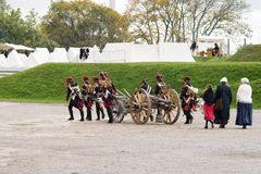 Napoleonic soldiers and their women are marching to a military camp. Napoleonic base with white tents.  Royalty Free Stock Photo