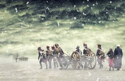 Napoleonic soldiers and women marching in falling snow and pulling a cannon in plain land, countryside with stormy clouds. Soldier Stock Images