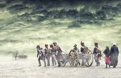 Napoleonic soldiers and women marching and pulling a cannon in plain land, countryside with stormy clouds. Soldiers going towards. A damaged abonded house Royalty Free Stock Photo