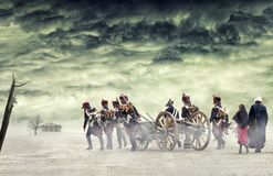 Napoleonic soldiers and women marching and pulling a cannon in plain land, countryside with stormy clouds. Soldiers going towards. A damaged abonded house Royalty Free Stock Image