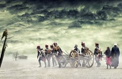 Napoleonic soldiers and women marching and pulling a cannon in plain land, countryside with stormy clouds. Soldiers walking. Napoleonic soldiers and women Stock Image