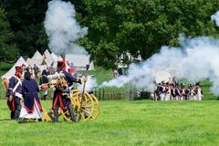 Napoleonic war re enactment. French Napoleonic artillery firing a cannon during a living history re enactment. French foot soldiers can be seen in the background Stock Image