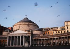 Napoli in in the South of Italy in the mornin. Napoli Basilica at Piazza del Plebiscito in the morning with flying seagulls stock images